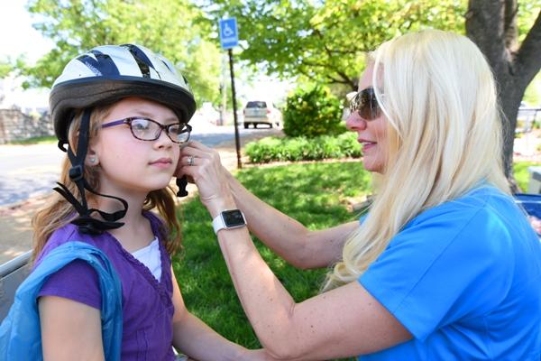 Sophia Vandervoort has her new bicycle helmet fitted by Julie Cappelletti of St. Louis Children's Hospital.
